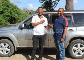 Here you are: Nyirenda (R) hands over the keys to Mtawali. In the background is the vehicle
