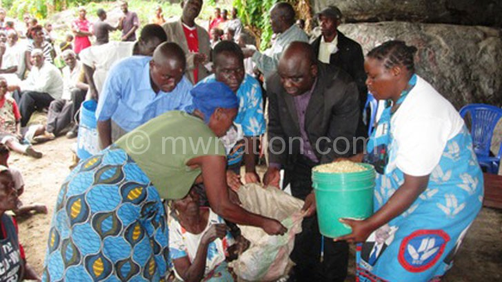 Kaunda (in black suit) helping with the donation