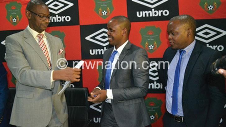 Nyamilandu (2ndR) and Mwenechanya shake hands and show off the sponsorship contract