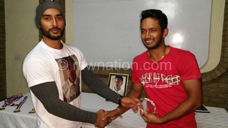 Bashir Junior's cousin Imran Aboobaker (L) presents trophy to Godambe