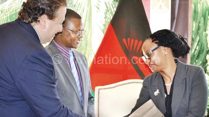 El-Adawy (L) presents an award to Mwale as Ndau (C) looks on