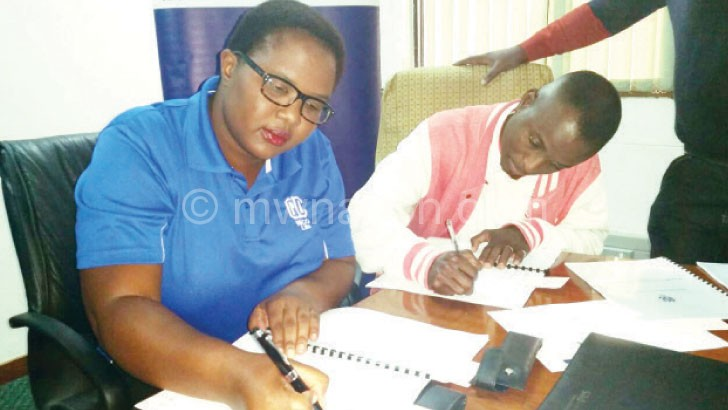 Lilian Moyo (L) and Kelvin Moyo sign the contracts