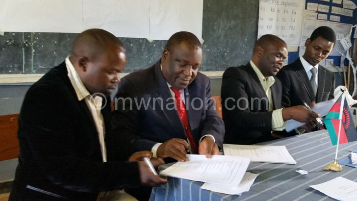 Thombozi (in red neck tie) signing the MOU while other members of the District Council Committee and CSOs look on.