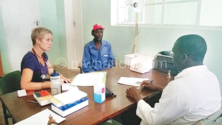 A patient (C) consults a geriatric expert (L) through an interpreter