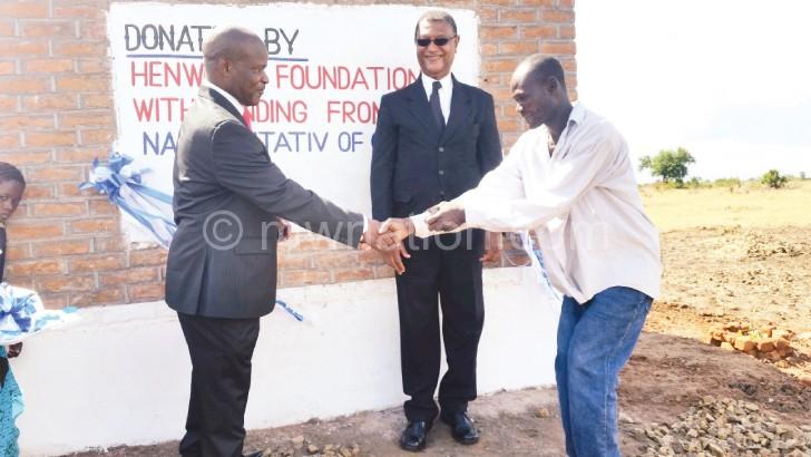Mandele (L) hands over the sanitary facilities to Mpungula as Mhango looks on