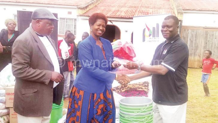 Kandango (R) makes a symbolic donation to Chidyaonga