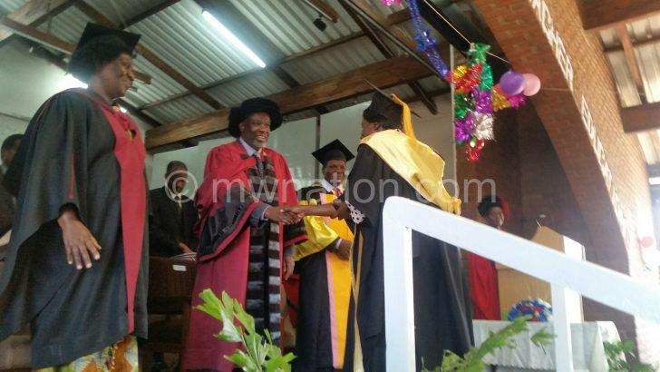 Saka (2nd L) congratulates one of the graduating teachers
