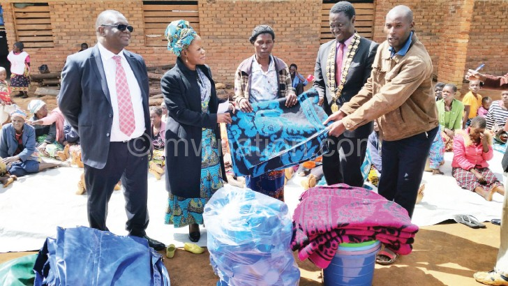 Mwapasa (2nd L) presents donation to Mkandawire (2nd R) as others look on
