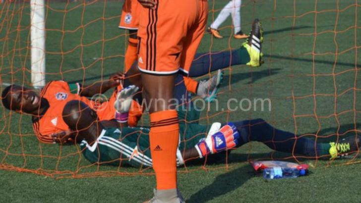 Nomads midfielder Mike Kaziputa (L) goalkeeper Phiri lies helplessly after conceding a goal against Mafco