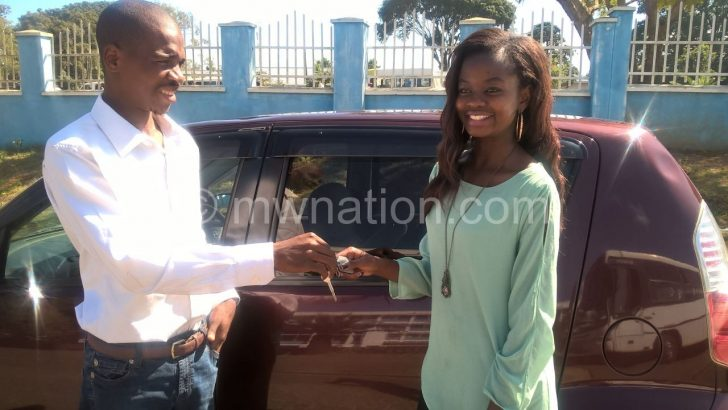 Miss BT recieving her car from Yanga.co manager