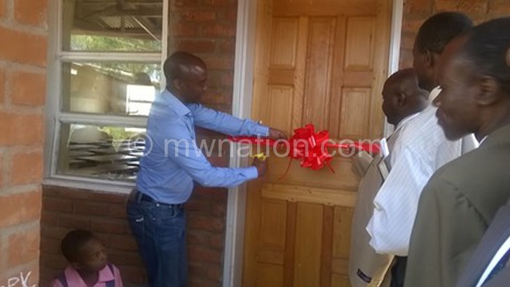 Kamoto cuts the ribbon to  mark the official handover