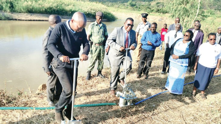 Chaponda and journalist Dalitso Chimwala (L) test the treadle pumps