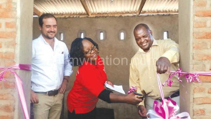 Parkinson (L), Kumwembe (C) and Kachere Prison OC cut the ribbon to the new kitchen