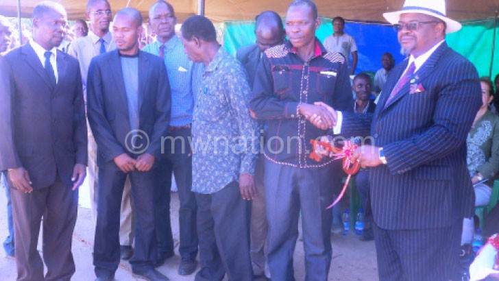 Msaka handing over a symbolic key