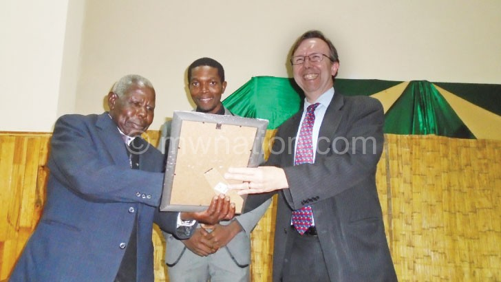 Mupa (L) recieves a certificate from Ridley