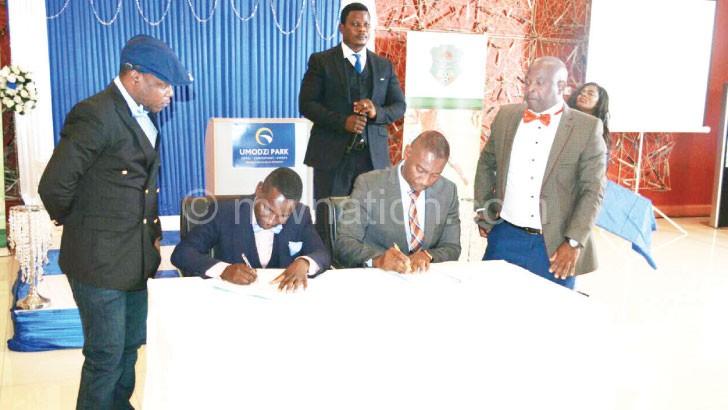 Nyamilandu (seated R) and Chirambo put pen to paper