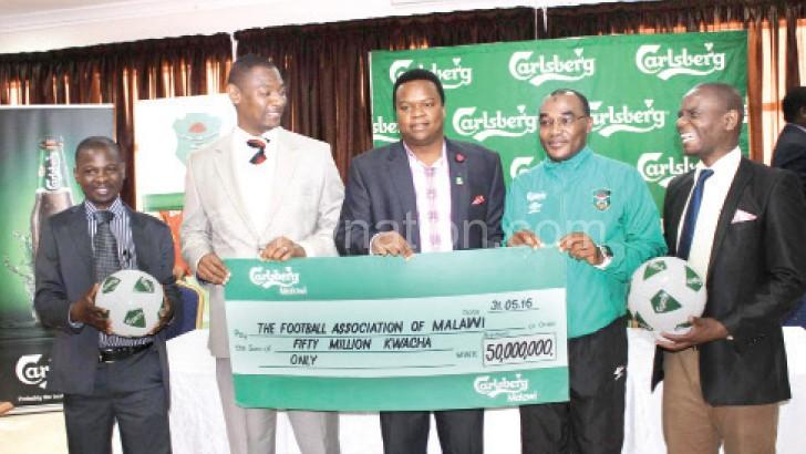 All smiles: Nyamilandu (L), Chirwa (2ndL), Ramadhan (2ndR) and FAM  commercial director Limbani Matola display the dummy cheque