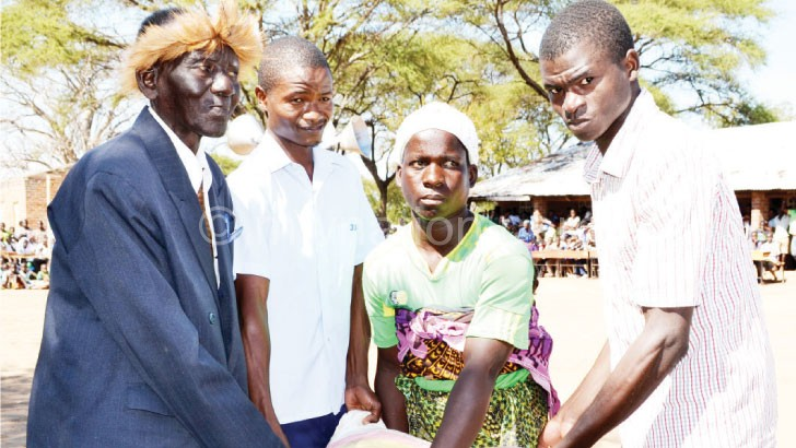 Likongwe (L) and a beneficiary receiving a bag of maize