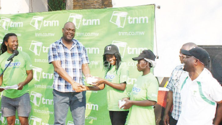 Malawi National Council of Sports exectuive secretary George Jana (L) hands over a prize to one of last year winners