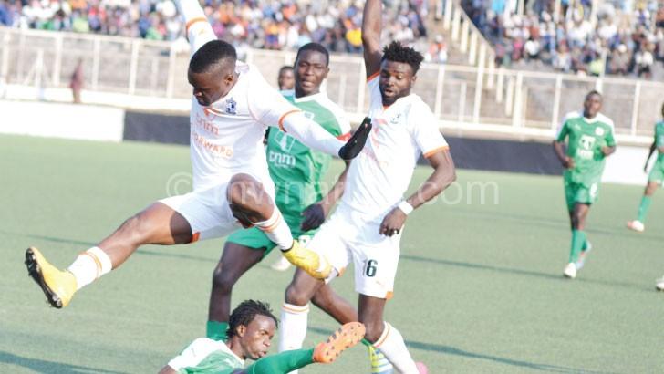 Mzuni's Bob Longwe (on the ground) stops Wadabwa during the match
