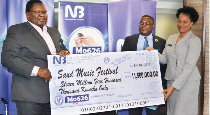 Banda (L) receiving the dummy cheque from Chirwa (R) as Mijiga looks on