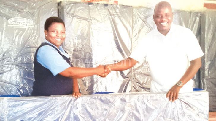 Harlod (L) presents mattresses and pails to QECH respresentative
