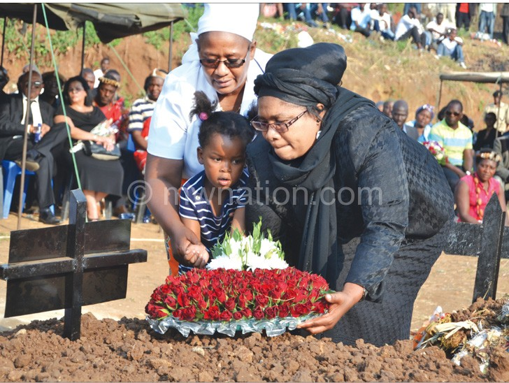 Mbendera's wife Aida, and a grandchild being assisted to lay a wreath by Ella Tsukuluza, wife of bishop Charles Tsukuluza, founder of Revival Life Church