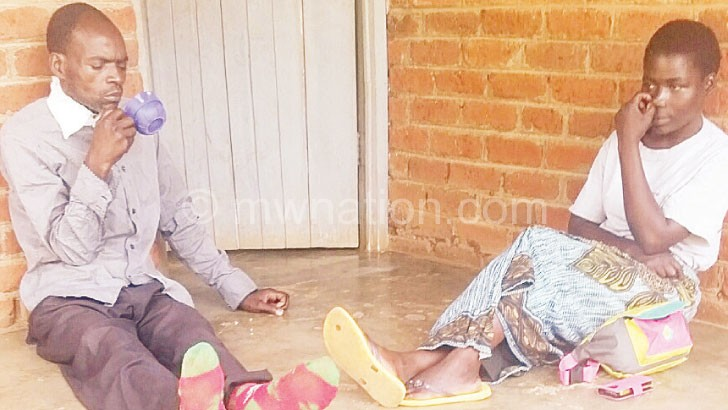Kamando (L) struggles to eat porridge as his wife looks on