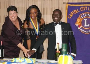 Palmer (L), Mwalweni (C) and Kaimvi cutting a cake during the event