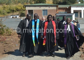 The clergy walk away from the new manse (in background) after  dedicating it to the Lord