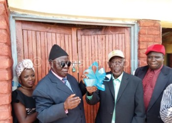 Senior Chief Kaluluma (C) raises the ribbon during the  handover ceremony of the village clinic
