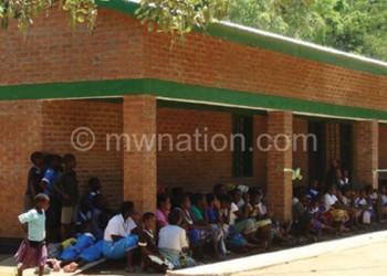 Pupils sit on the veranda of the new classrooms blocks