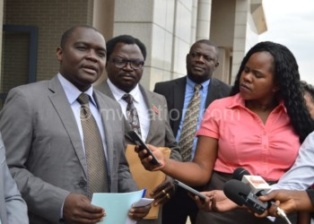 Meja (L) addresses journalists as MP Bon Kalindo (2nd L) and Mkwezalamba  (2nd R) look on