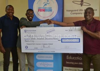 Mwakikunga hands over the cheque to Kambewa while Mwantisi look on