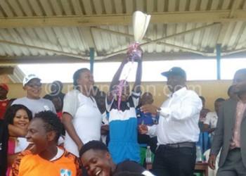 DD Sunshine's Mwale hoists the trophy as Mwenda (2ndR) and Ngwira look on