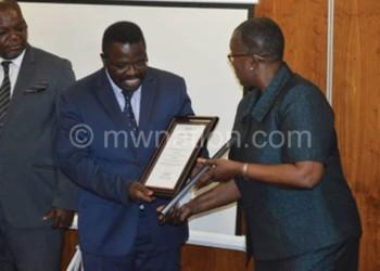 Zhuwawo (L) looks on as Amosi (C) receivs the accreditation certificate from Mutasa (R)