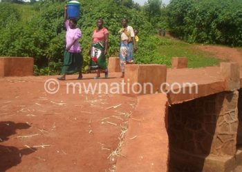 Women cross a bridge constructed with CDF funds