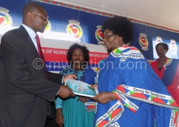 Ngoma (R) hands over a copy of the Nonm constitution to Simeza