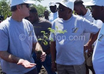 Mc Alpine (L) explains to Masi before planting trees