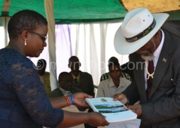 Botoman (L) presents the blueprint to Senior Chief Kapeni