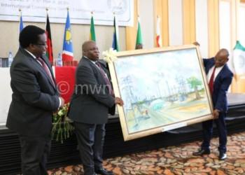 Kutsaira receives a gift from Chiwaya as PS Patrick Matanda looks on