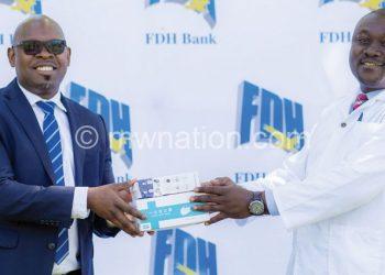 Msapato (L ) hands over the donation to Kawalazira
