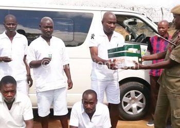 A warder and Kaonga make a sympbolic presentation of a donation from Mzuzu University