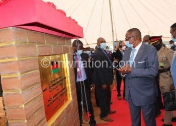 Mutharika (C) being shown the design of the Bullets stadium