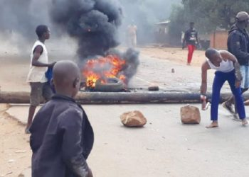 Some youths block the road for a politician not to pass