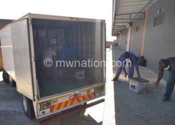Officials load ballot boxes from MEC warehouse into a van