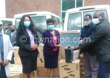 Maneb officials make a symbolic presentation to Nyalonje (3R)