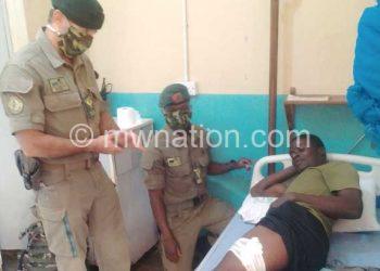 Munro (standing) cheers Kalonga in hospital