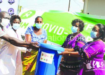 Mihowa (far R) presents Covid-19 prevention tools at Chambe Health Centre in Mulanje