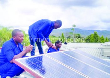 Kankulungo (C) and his team assemble solar panels for the power boosting system